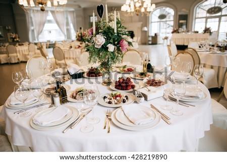 Elegant wedding reception white table arrangement, floral centerpiece decoration, restaurant - stock photo