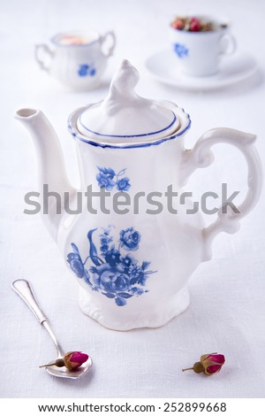 Elegant white blue teapot with small spoon with roses bud and sugar bowl and teacup background - stock photo