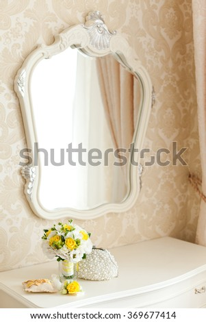 Elegant white commode with beautiful mirror and yellow wedding bouquet on it - stock photo