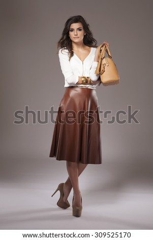 Elegant woman holding a brown purse