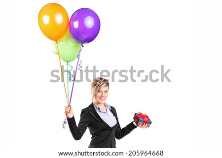 Elegant woman holding a present and a bunch of balloons isolated on white background - stock photo