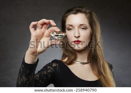 Elegant woman holding giant diamond - stock photo