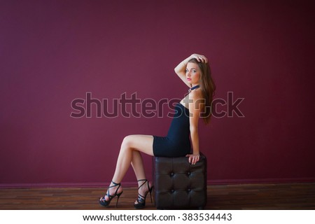 Elegant woman in a black dress sitting on the ottoman. Fashion photo shoot in the studio.
