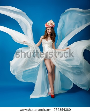 Elegant woman in a flowing white dress on a blue background