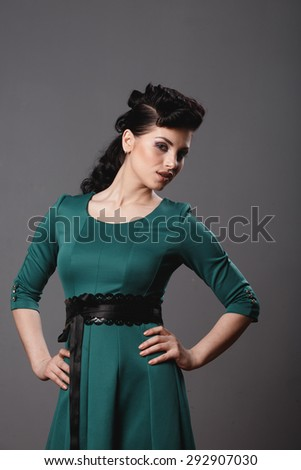 Elegant woman in a green dress beautiful hair studio - stock photo