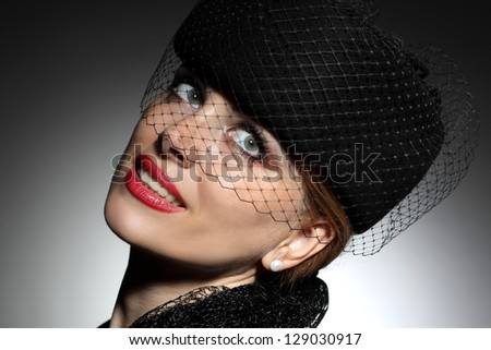 elegant woman in a hat on grey background