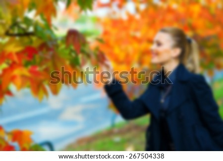 elegant woman in autumn scenery, blurred for presentation, abstract background - stock photo