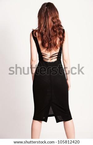 elegant woman in black dress back  studio shot - stock photo
