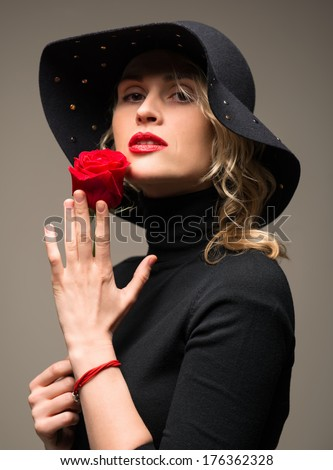 Elegant woman in black  hat  with red rose