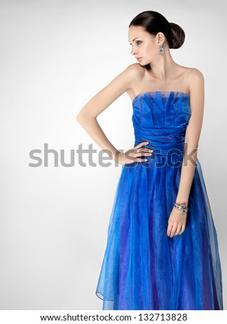 elegant woman in blue silk evening dress - stock photo