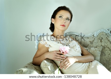 Elegant woman in evening gown with a flower - stock photo