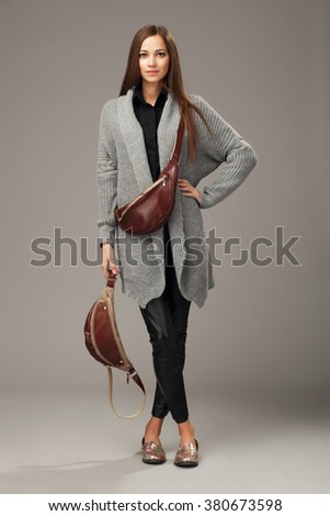 Elegant woman in gray woven cardigan with two leather fanny packs