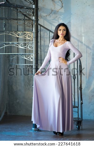 Elegant woman in luxury long violet dress standing near stairs