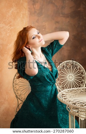 Elegant woman in retro style sitting at the table. Relax, stretches. - stock photo