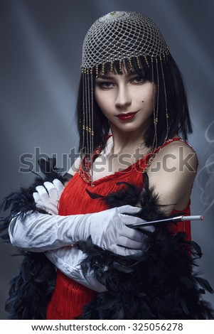 Elegant woman in the red dress and necklet. Retro style. Old fashion. Girl smokes with a mouthpiece. Toned.  - stock photo