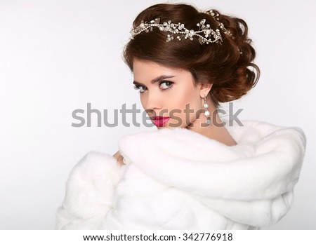 Elegant woman in white fur coat. Wedding Hairstyle. Beautiful fashion bride girl model portrait. Luxury jewelry. Attractive young woman with brown hair. - stock photo