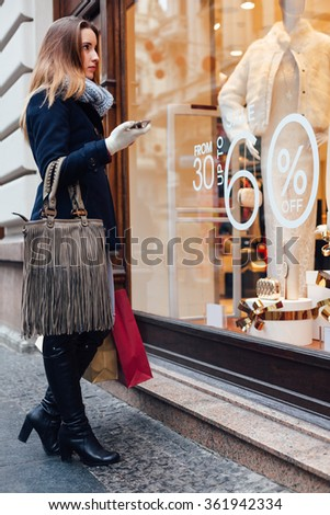 Elegant woman looking at boutique showcase with a discount - stock photo