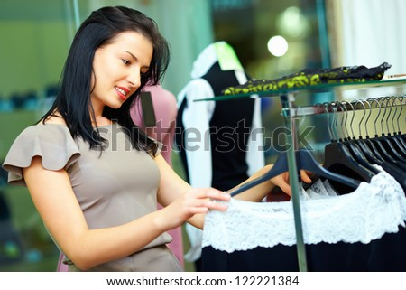 elegant woman looking for dress in clothing store