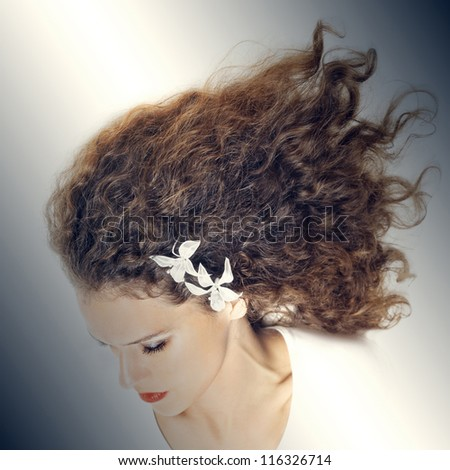 Elegant woman portrait with curly hair. Young woman hairstyle