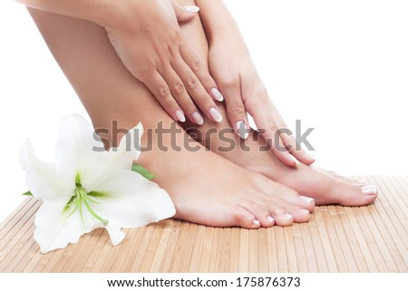 Elegant woman's hand with manicure and feet with pedicure madonna lily on bamboo mat. Relaxing pedicure and manicure with white madonna lily flower. Beautiful manicure and pedicure.