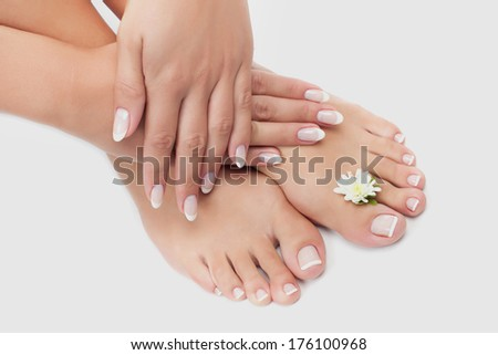 Elegant woman's manicured hand and pedicured feet with flower - stock photo