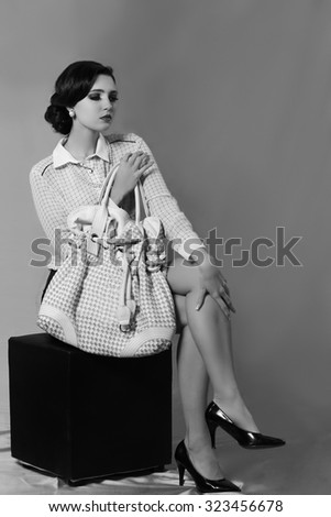 Elegant woman seated on black chair holding white handbag - stock photo