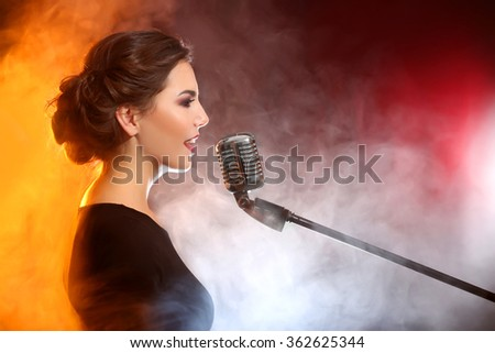 Elegant woman singing in colourful smoke, close up