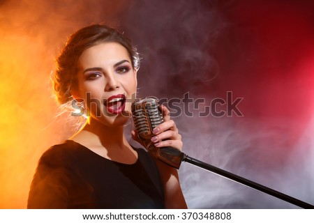 Elegant woman singing in colourful smoke, close up - stock photo