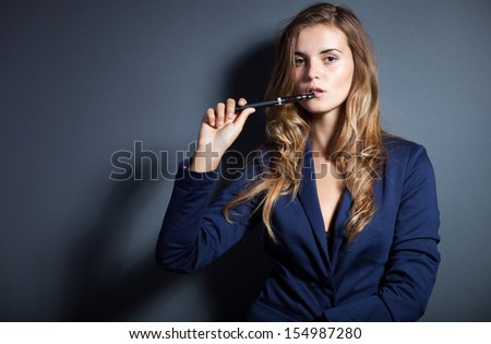 Elegant woman smoking e-cigarette, wearing suit - stock photo