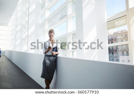 Elegant woman using mobile phone after work on digital tablet while standing in office interior,female manager read text message on cell telephone while waiting for her colleague after finish work day - stock photo