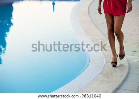 Elegant woman walking by the pool, close-up of her legs - stock photo