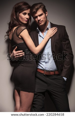 Elegant woman wearing a black dress embracing her lover while he is leaning on a dark grey wall with one hand in his pocket. - stock photo