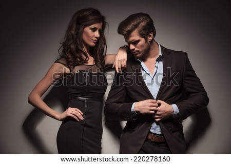Elegant woman wearing a black dress looking and leaning on her boyfriend while the man is unbuttoning his brown jacket. Both looking away from the camera. - stock photo