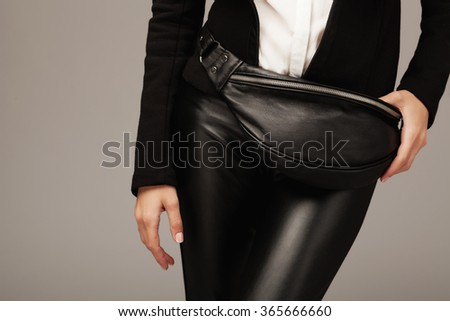 Elegant woman with a black leather fanny pack - stock photo
