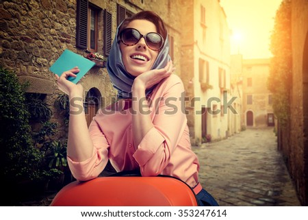 Elegant woman with a suitcase travel and ticket on street of italian city - stock photo