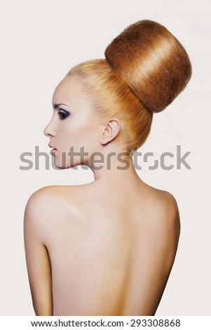 elegant woman with creative hair style. Fashion woman model with creative huge bun hairstyle with big chignon. Beautiful shiny volume hair - stock photo