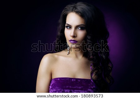 Elegant woman with curly hair and violet light