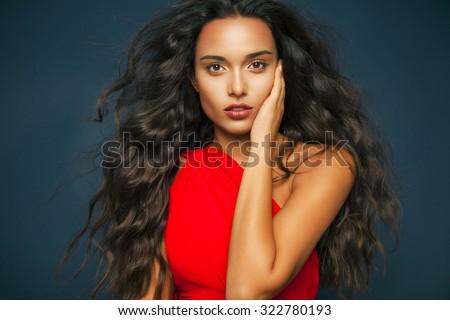 người phụ nữ thanh lịch với mái tóc lượn sóng dài và đôi môi đỏ mặc váy đỏ.  Thời trang và mỹ phẩm phòng thu shot, ngang