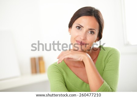 Elegant woman with natural beauty in green shirt smiling at her house - copyspace - stock photo