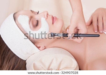 Elegant woman with perfect skin on her face,the girl with eyes closed receiving beauty treatments.Girl with dark hair lying on her back in the beauty salon.Beauty.Female face with a white mask.  - stock photo