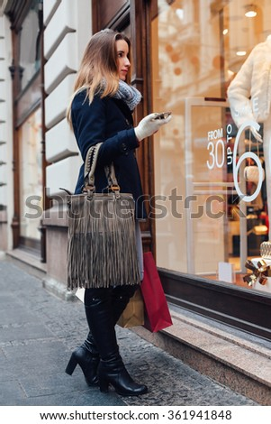 Elegant woman with scarf and winter gloves looking at boutique showcase - stock photo