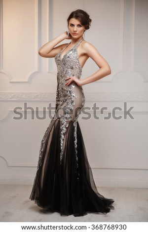 Elegant woman with smart beautiful hairstyle in the beige satin evening sparkling dress and with expressive make up is posing in the interior studio - stock photo
