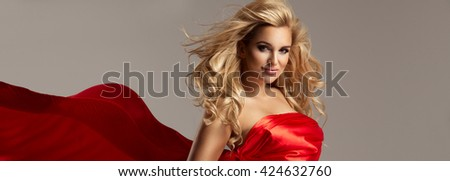 Elegant woman with wavy red dress posing in proud