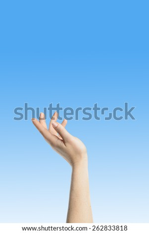 Elegant womans hand reaching blue peaceful sky