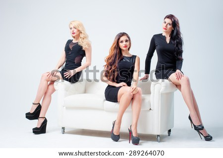 Elegant women. Group portrait of three attractive caucasian models wearing black dresses sitting on the white sofa - stock photo