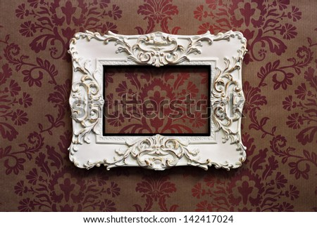 Elegant wooden frame with Victorian style wallpaper as background. - stock photo