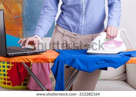 Elegant working woman during ironing at home - stock photo