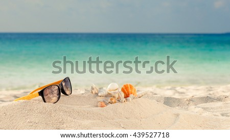Elegant yellow and black women's sunglasses with shell at the beach - stock photo