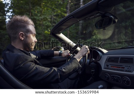 Elegant young attractive man in convertible car outdoor. - stock photo