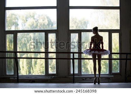 Elegant young ballerina standing near a large window in a dance class. Relying on the dance machine looks somewhere. Silhouette against a window. - stock photo